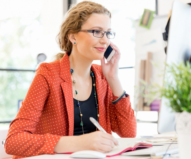 young-woman-holding-mobile-phone-in-office-PE9ARDR